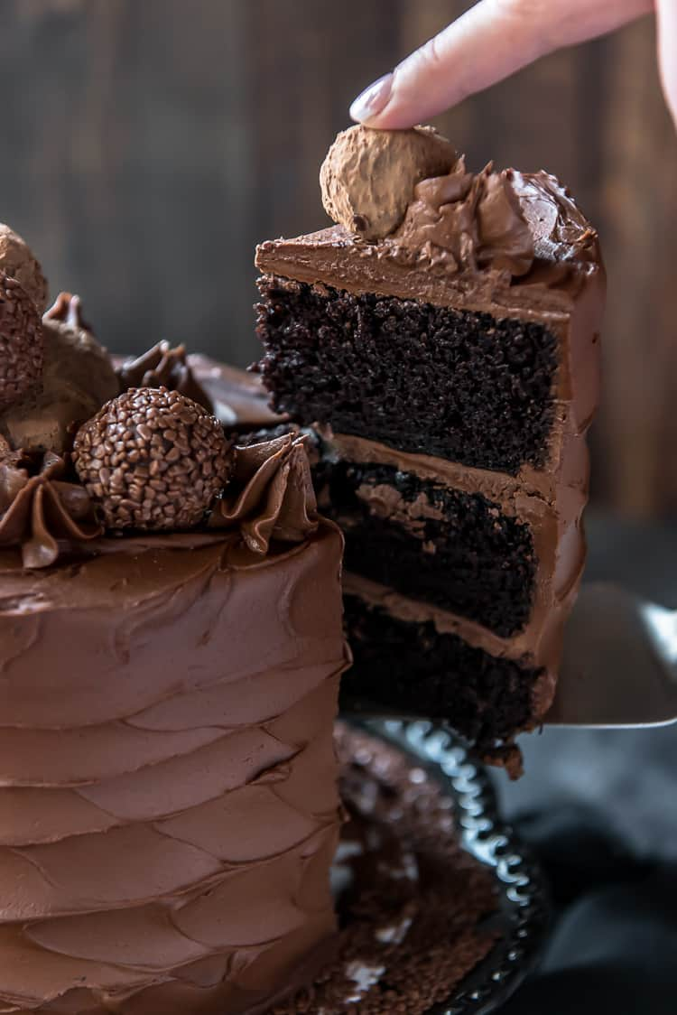 Lifting a slice away from a Triple Chocolate Cake