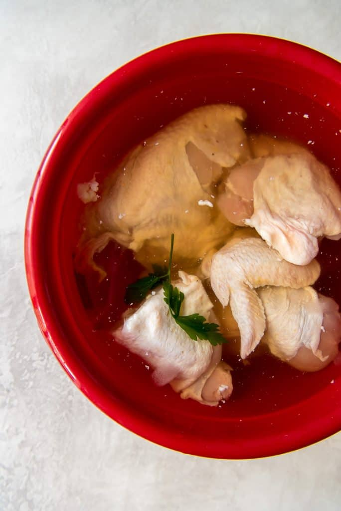 Raw chicken in a bowl of brine