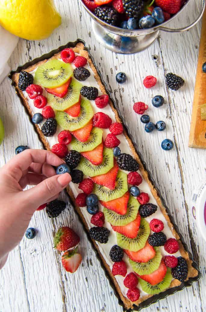Placing berries on a Whipped Yogurt Fruit Tart