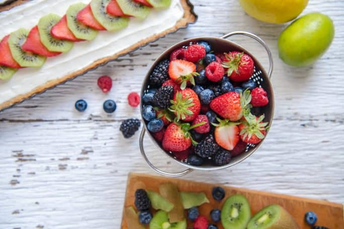 A bowl of assorted berries and a fruit tart