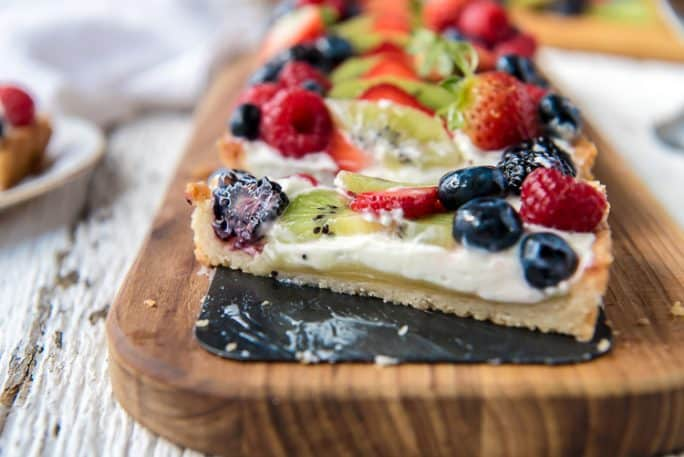 Whipped Yogurt Fruit Tart with a slice cut out of it