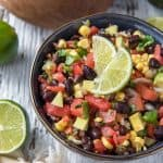 Mexican Avocado Black Bean and Corn Salsa in a bowl with lime slices
