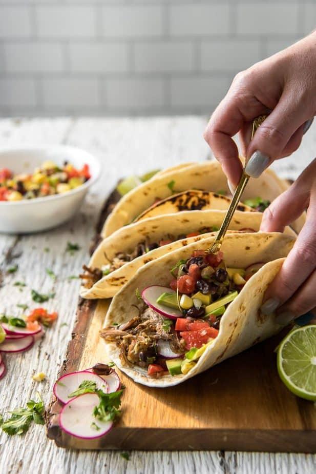 Spooning Instant Pot Carnitas into tacos