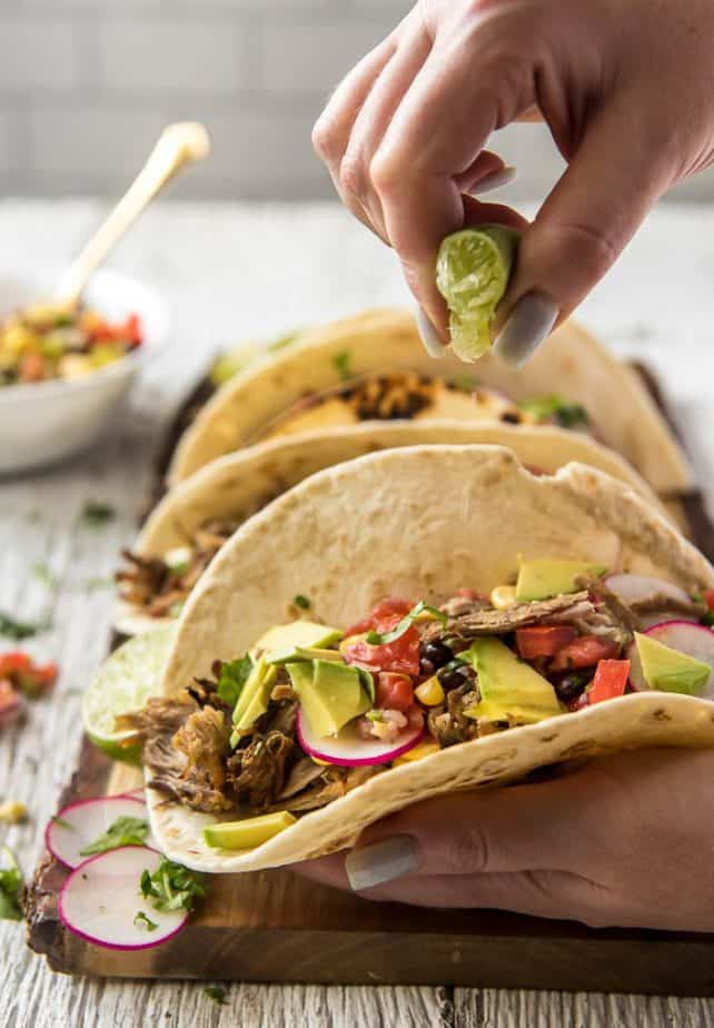 Instant Pot Carnitas Tacos with lime wedges