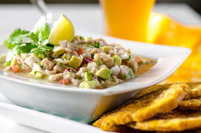 A bowl of Margarita Ceviche with fried green plantains