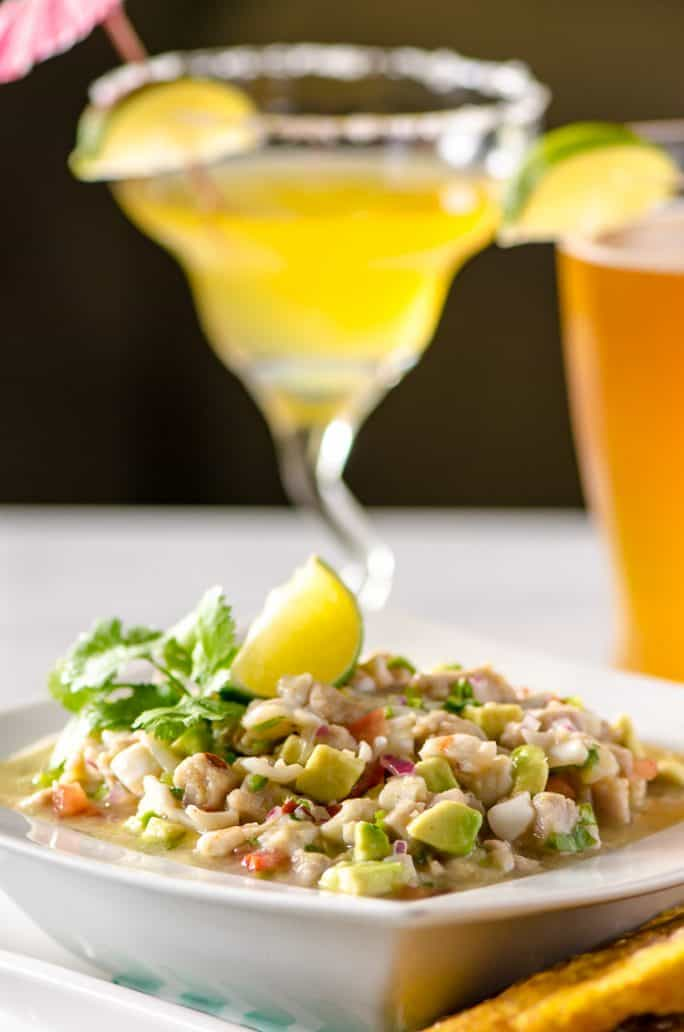 Margarita Ceviche in a bowl with margaritas and beer in the background