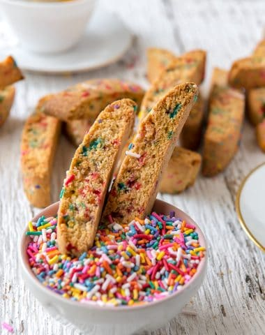 Rainbow biscotti in a bowl of sprinkles