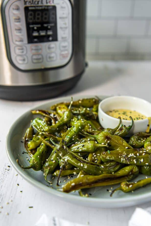 A plate of Blistered Shishito Peppers with an Instant Pot behind it