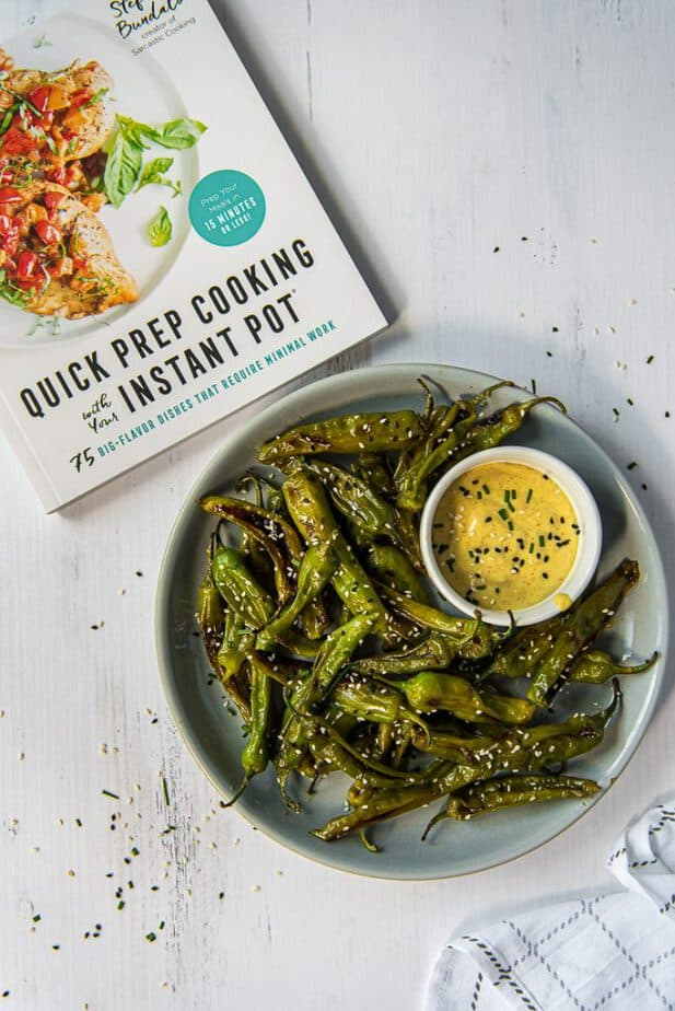Instant Pot Blistered Shishito Peppers on a plate with a cookbook next to it