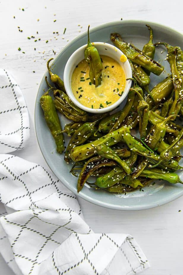 Instant Pot Blistered Shishito Peppers on a plate with a dipping sauce