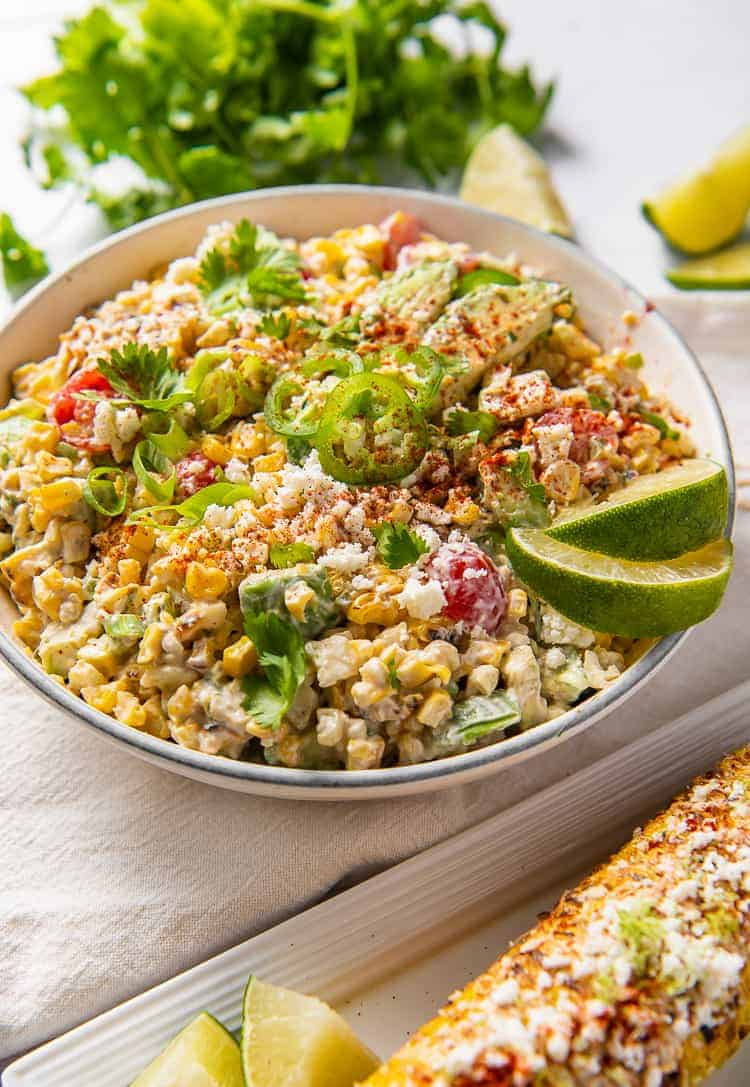 Mexican corn salad in a bowl with a corn cob