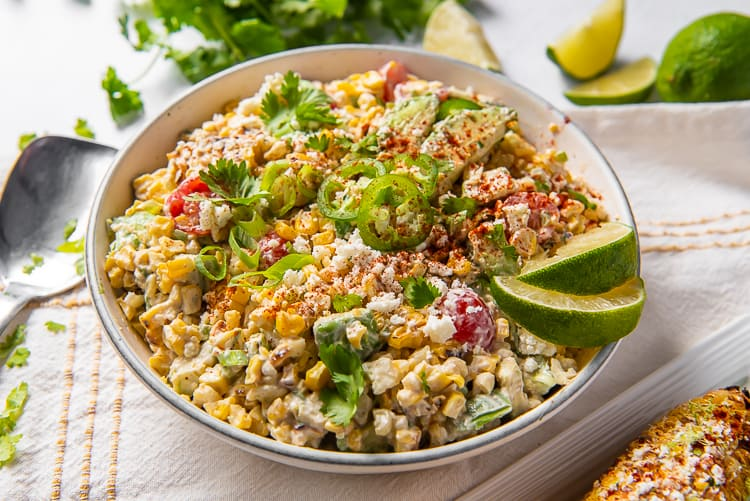 Mexican Street Corn Salad topped with jalapeno and lime in a bowl