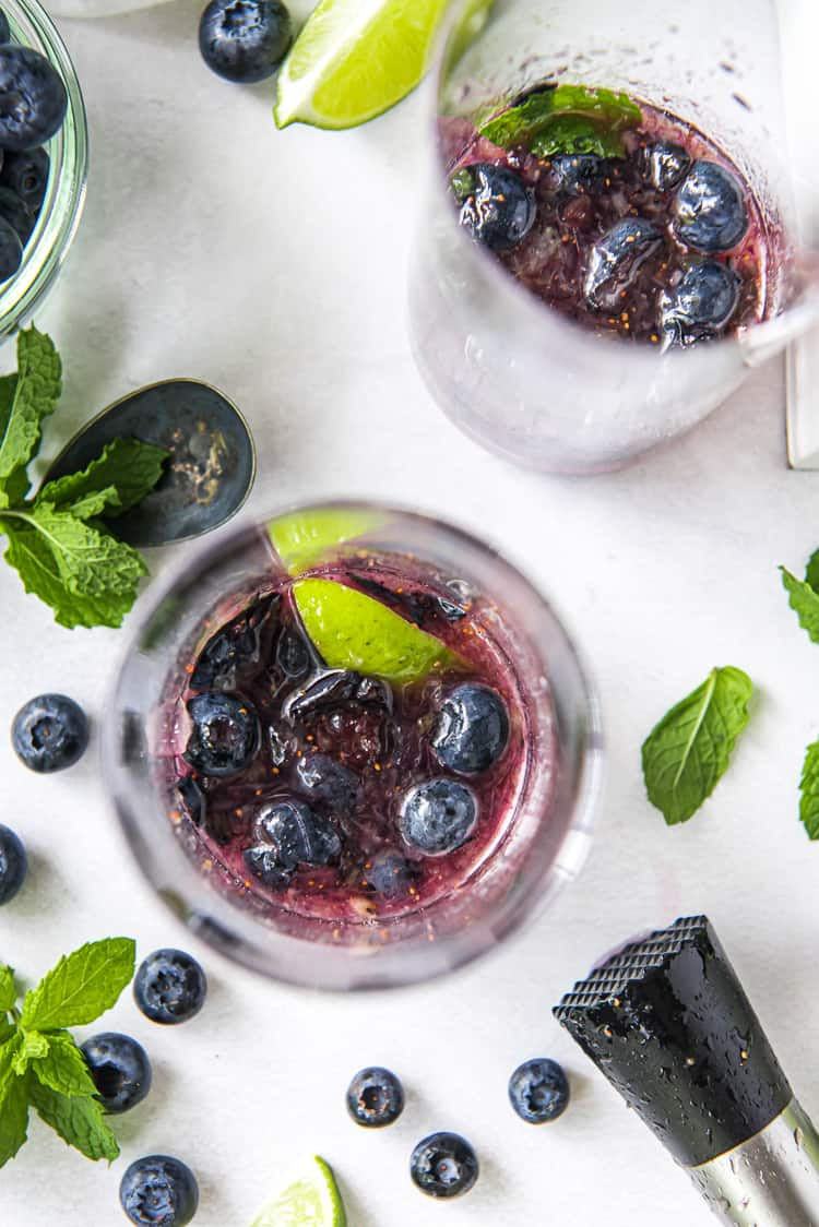 muddled blueberries and lime wedges in a highball glass