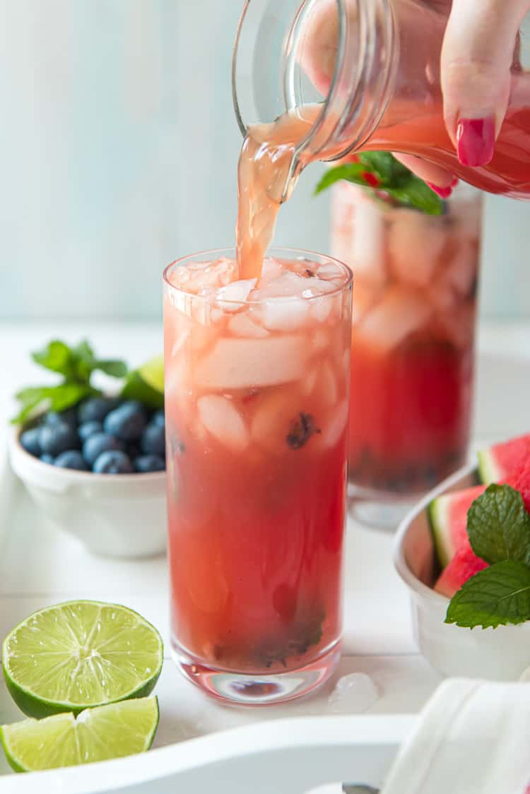 Pouring watermelon agua fresca into a glass