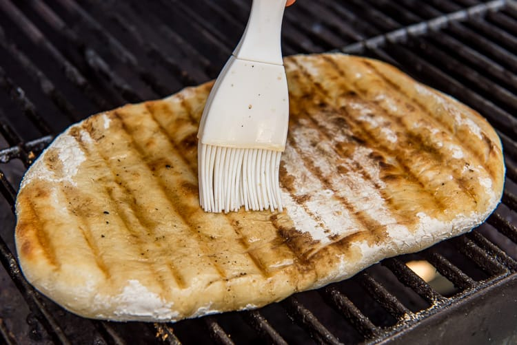 brushing oil on grilled pizza dough