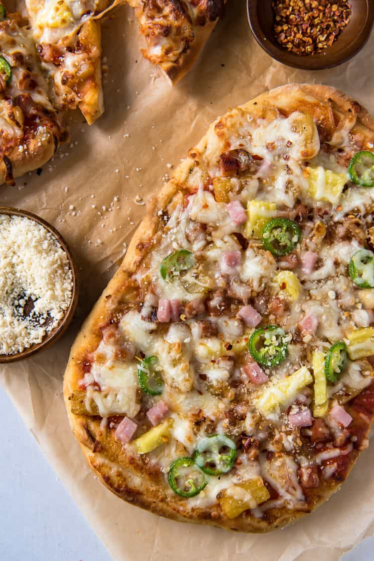 Grilled Hawaiian Pizza with cheese and red pepper flakes