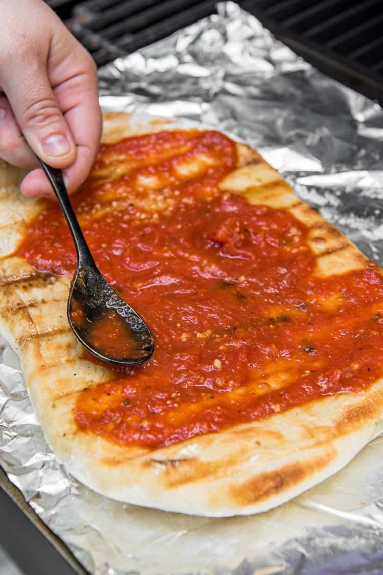 spreading sauce on grilled pizza dough