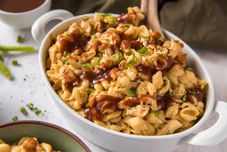 BBQ chicken mac and cheese in a white serving dish with a spoon