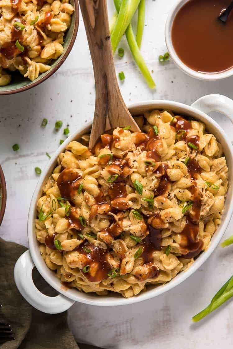 BBQ chicken macaroni and cheese in a white serving dish with a spoon