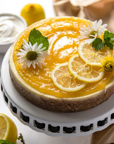 an Instant Pot Lemon Ricotta Cheesecake on a cake stand