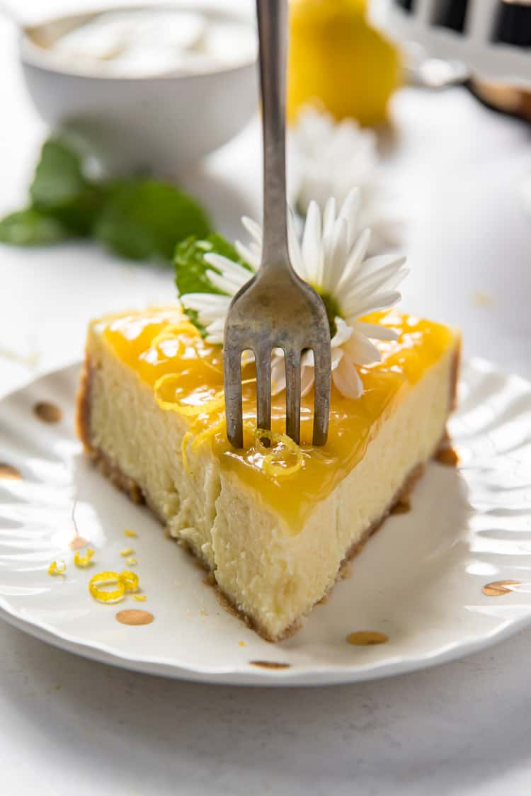 A slice of lemon ricotta cheesecake on a plate with a fork in it