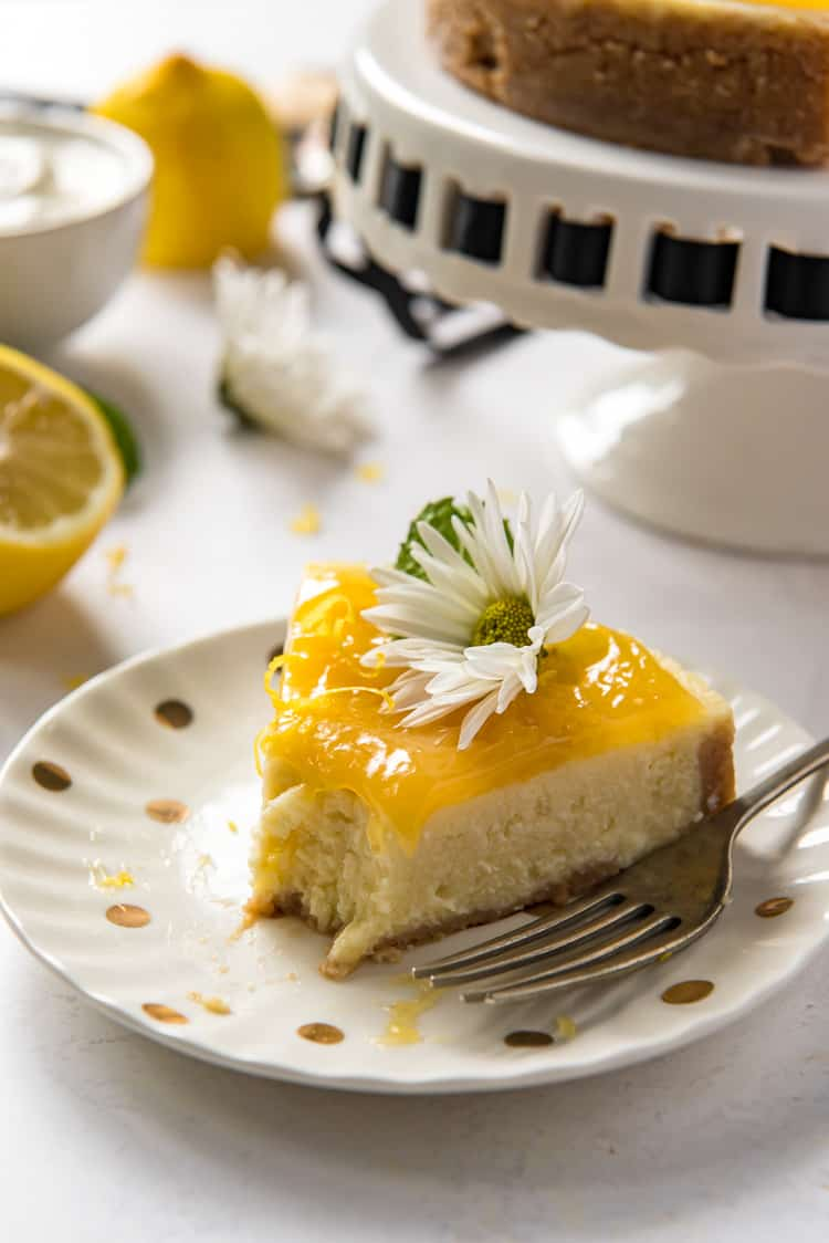 A slice of lemon ricotta cheesecake on a plate with a bite taken out