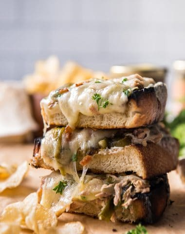A stack of open-faced tuna melt sandwiches with potato chips