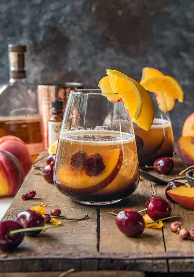 a peach old fashioned cocktail on a wood tray