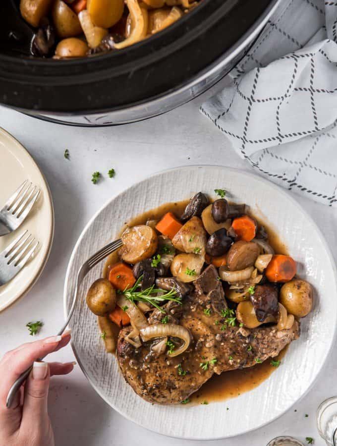 crock pot pork chop on a plate with vegetables