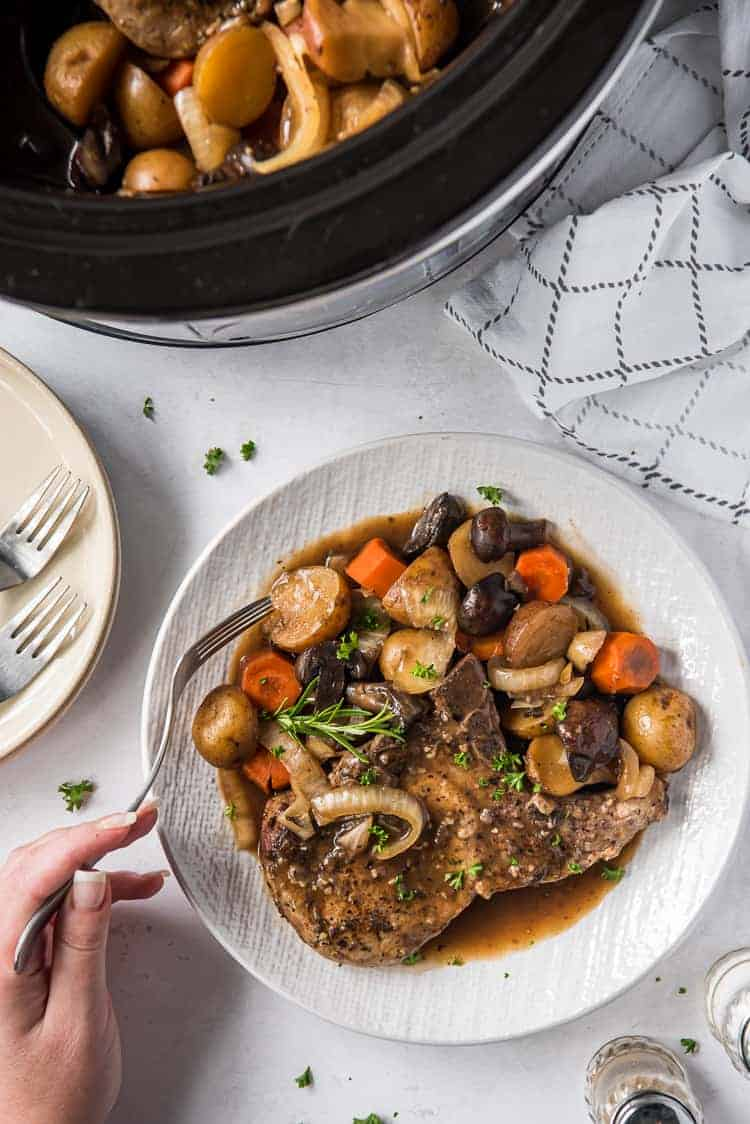 crock pot pork chop on a plate with vegetables