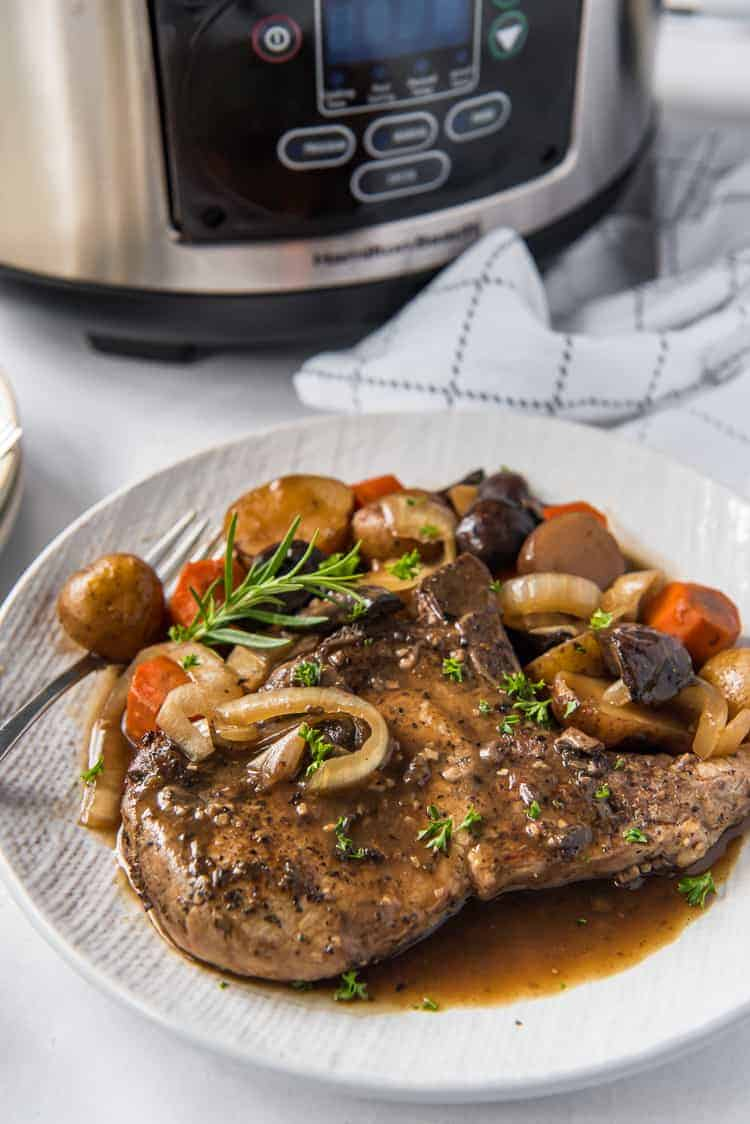 smothered pork chops made in a slow cooker on a plate
