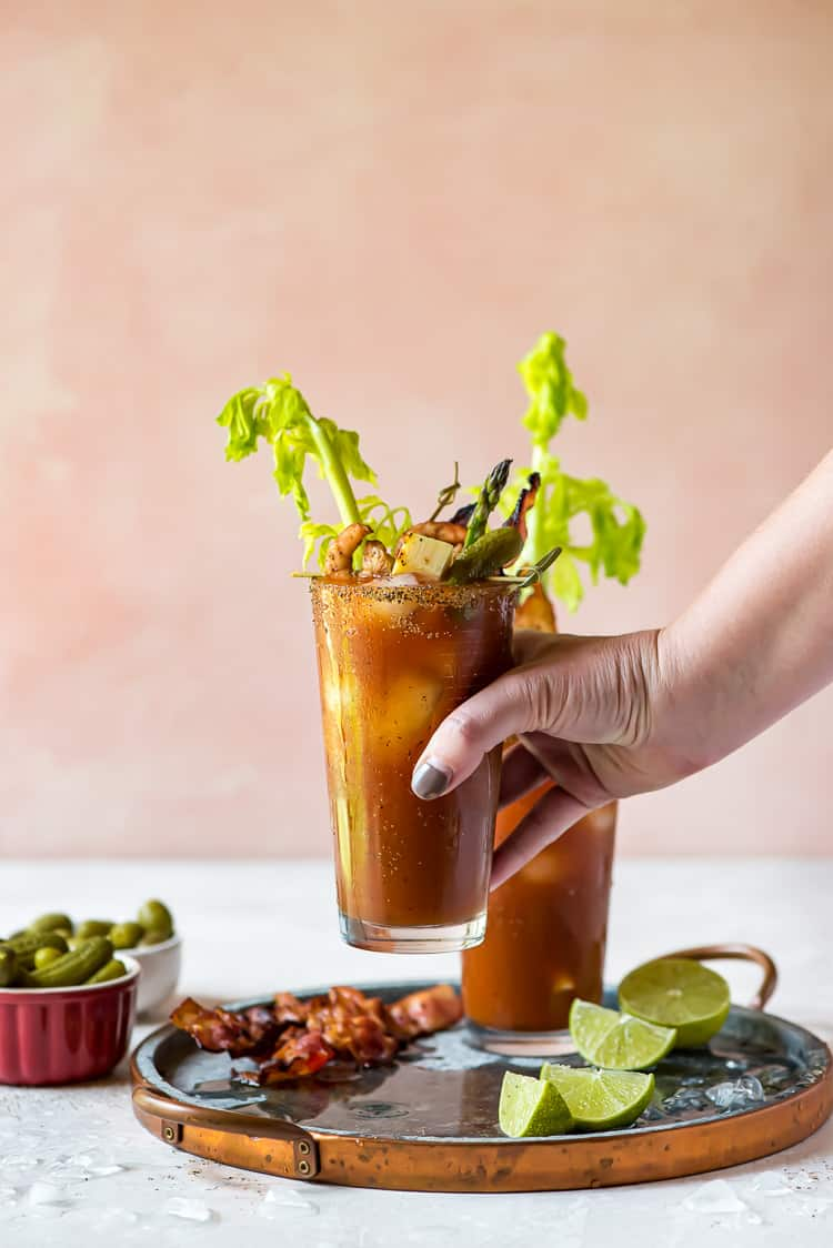 A hand grabbing a Bloody Mary from a tray