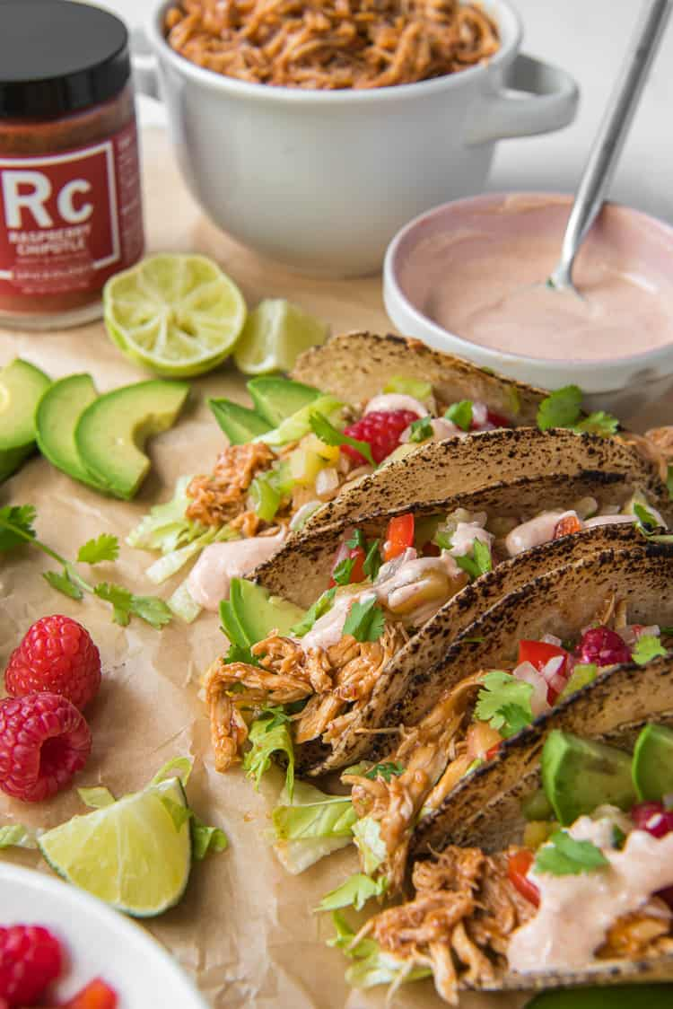Slow cooker Raspberry Chipotle chicken tacos made in the slow cooker on brown parchment with bowls of crema and shredded chicken