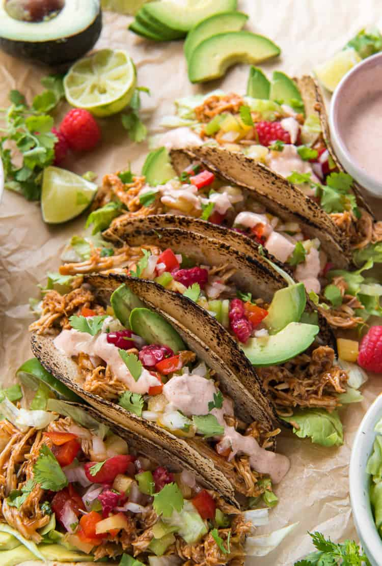 Top shot of Slow Cooker Chicken Tacos garnished with raspberries and avocado