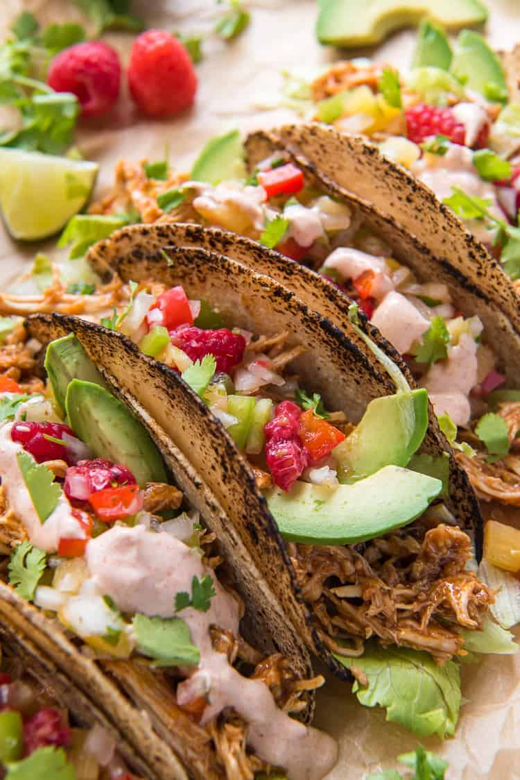 Raspberry Chipotle Slow Cooker Chicken Tacos garnished with raspberries and avocado