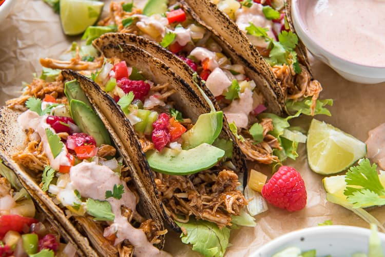 Slow Cooker Chicken Tacos garnished with raspberries and avocado