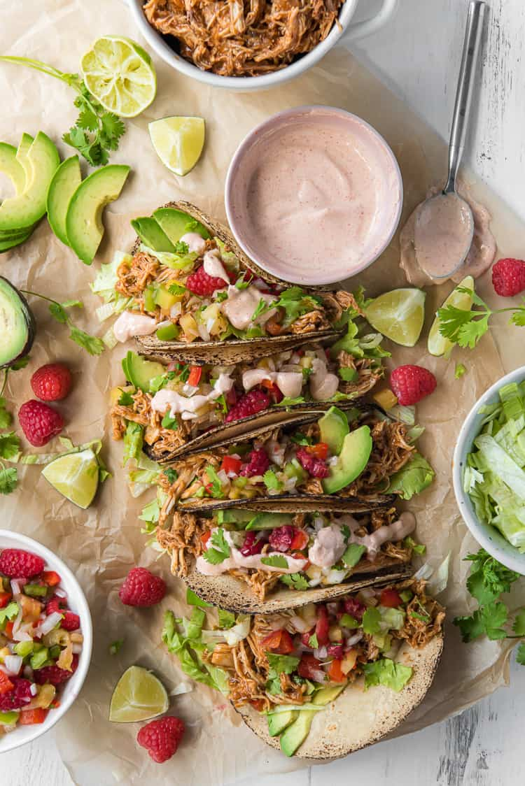 A spread of Chicken Tacos garnished with raspberries and avocado