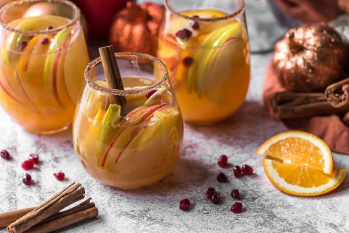 3 wine glasses filled with pumpkin sangria