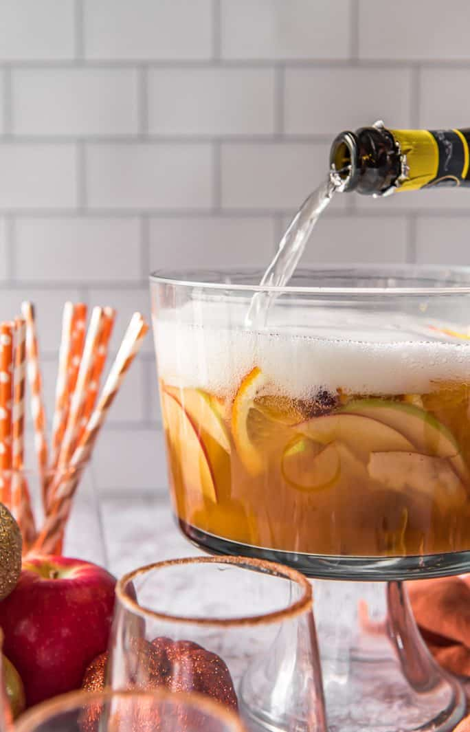 pouring Prosecco into a punch bowl filled with pumpkin sangria and apples