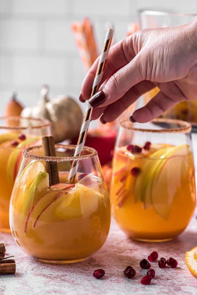 a hand placing a straw in a wine glass filled with pumpkin sangria