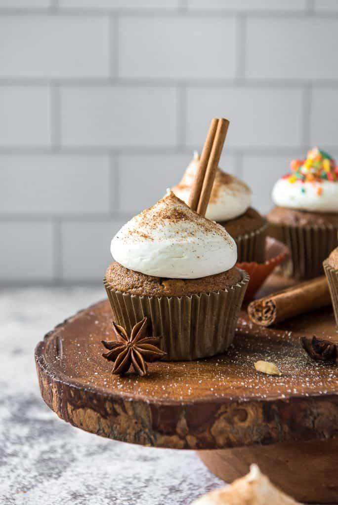 chai pumpkin cupcakes on a wood slice cake stand