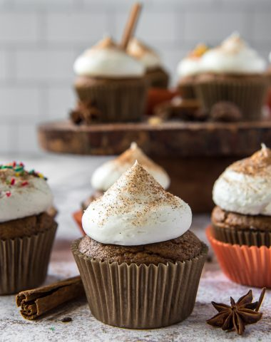 chai pumpkin cupcakes on a wood slice cake stand
