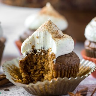 a chai pumpkin cupcake with a bite taken out of it