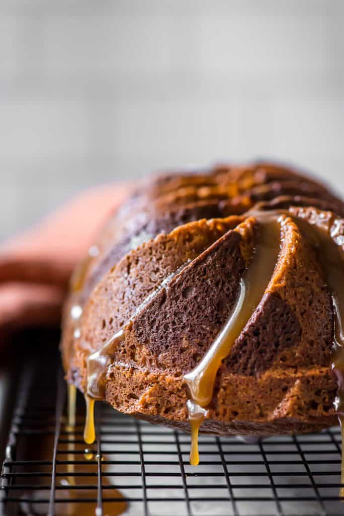 bourbon glaze dripping down a swirled chocolate pumpkin bread loaf
