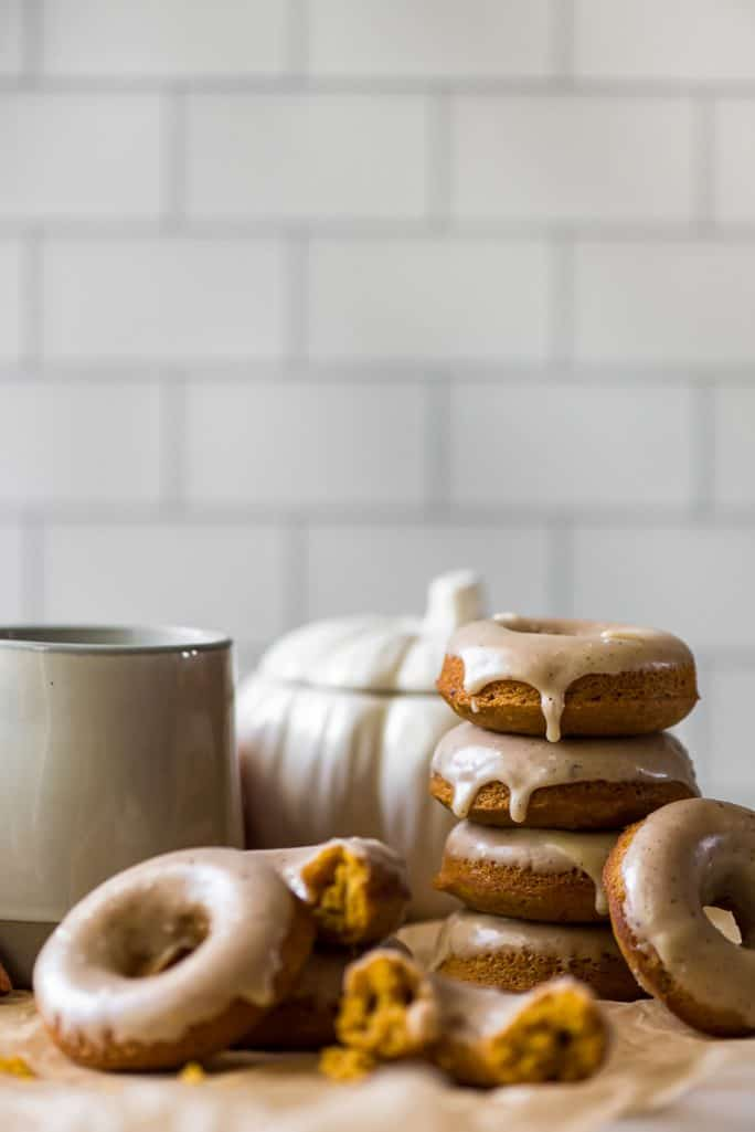 a stack of baked pumpkin donuts next to a cup of coffee