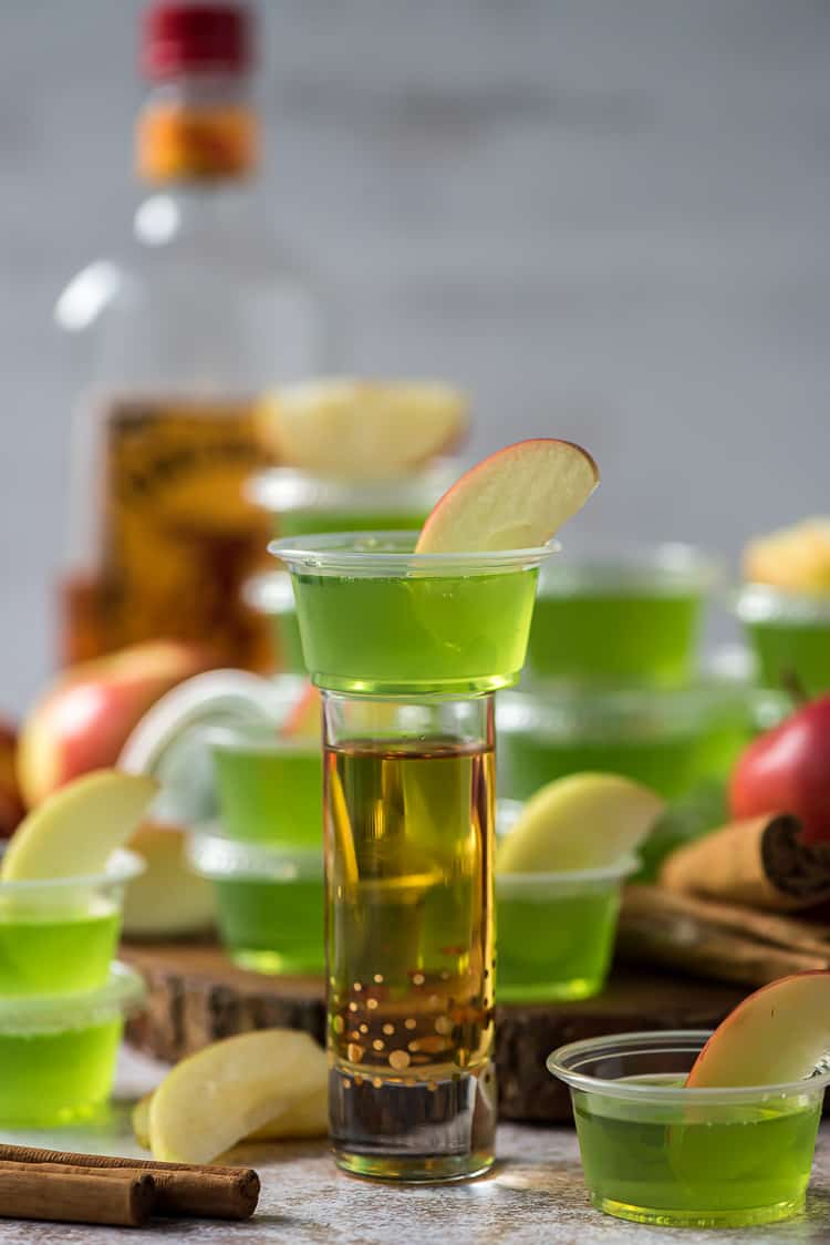 a cinnamon apple jello shot cup on top of a shot glass full of cinnamon whiskey