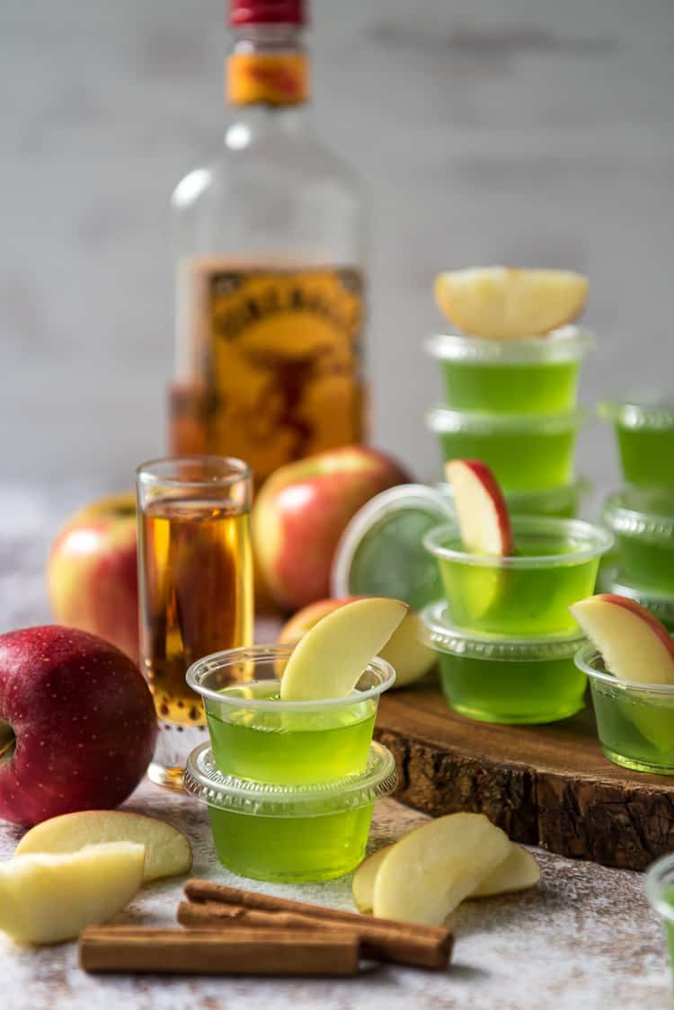 a stack of apple jello shots with apple slices in them, and a bottle of fireball whiskey in the background