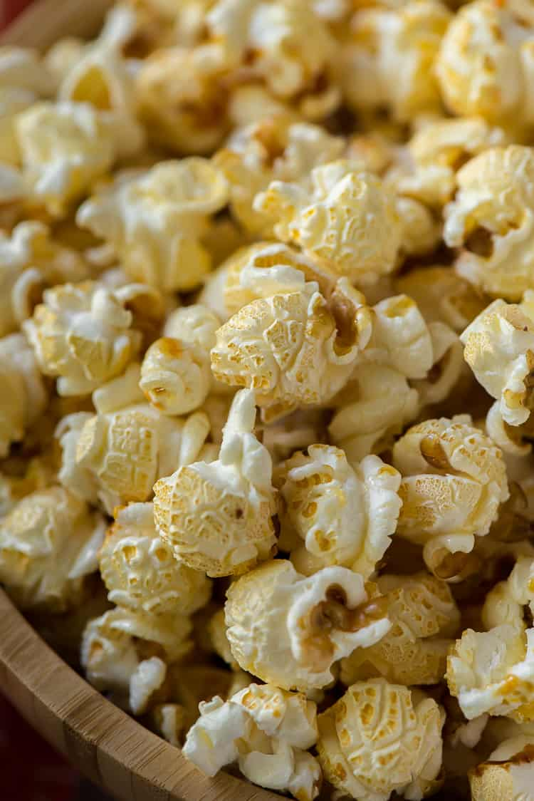 a closeup of popped kettle corn in a wooden bowl