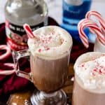 2 mugs of spiked peppermint hit chocolate, with a bottle of vodka and peppermint scnapps in the background