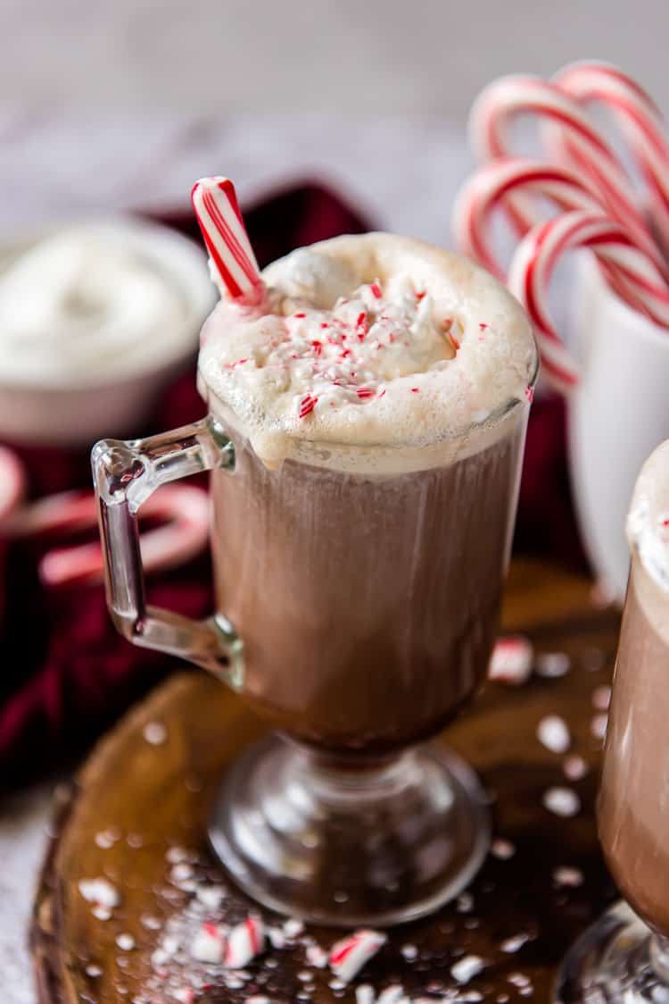 a mug of boozy hot cocoa with a peppermint stick in it